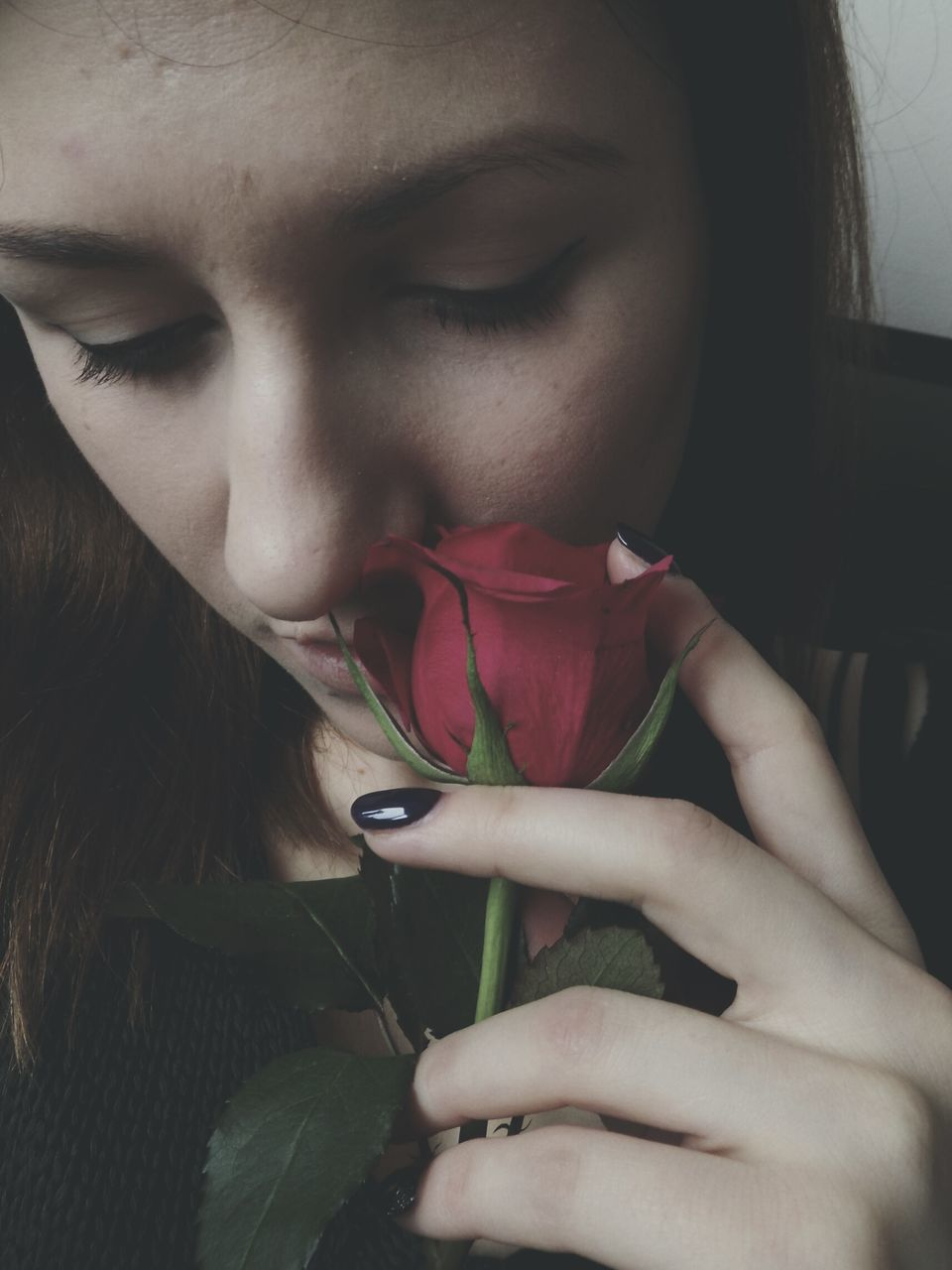 Close-Up Of Young Woman Holding Red Rose