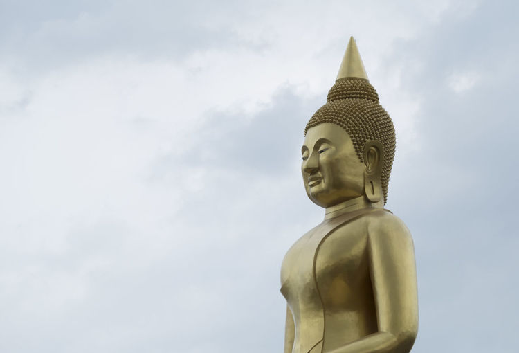 The lord Buddha statue with blue sky background Ancient Buddha Copy Space Golden The Lord Buddha, Architecture Art And Craft Belief Blue Sky Background Built Structure Cloud - Sky Creativity Human Representation Idol Landmark Low Angle View Male Likeness No People Place Of Worship Religion Representation Sculpture Sky Spirituality Statue
