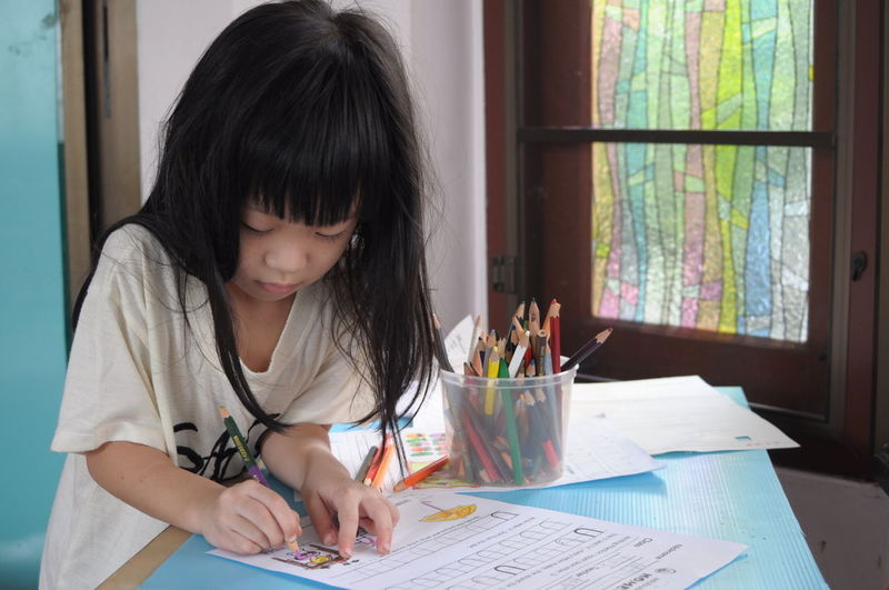 Girl Drawing Child Headshot Paper Sitting Concentration Domestic Life Looking Down Writing Curtain Casual Clothing Paintbrush Art Studio Colored Pencil Art Class Pencil Shavings Acrylic Painting