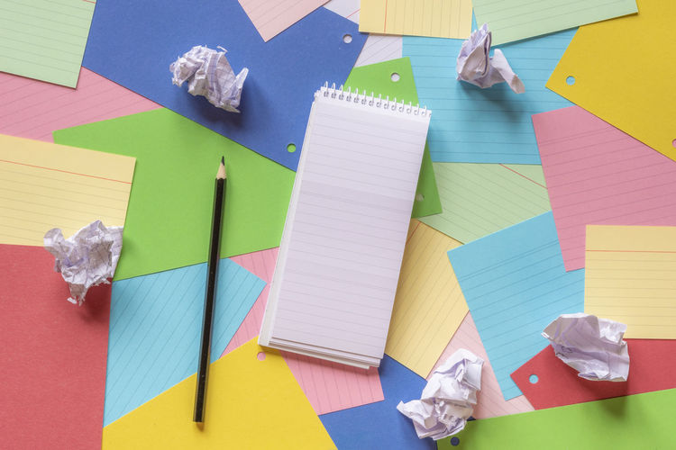 High Angle View Of Colorful Papers And Pencil On Table