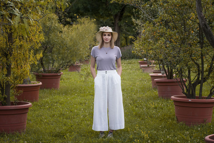 Portrait of woman standing by plants against trees