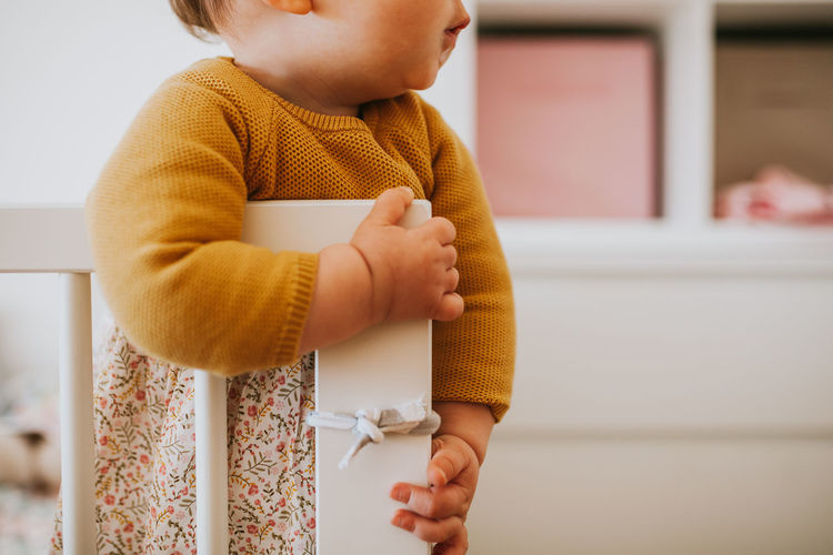 Yellow Crib Baby Child Daughter Childhood Dress Family Matters Family With One Child Lifestyles Girl Indoors  Midsection Real People One Person Standing Young Innocence Front View Home Interior Men