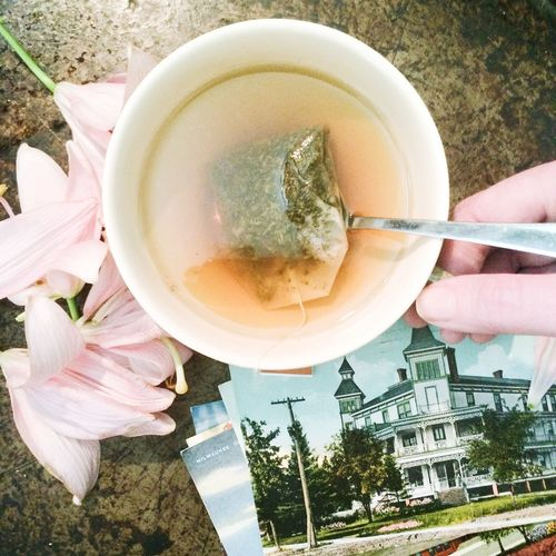 Cropped image of hand holding tea cup by photographs and flowers