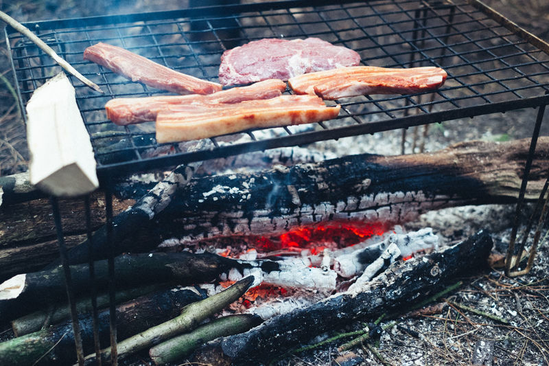 Camping Backwoods Barbecue Barbecue Grill Bonfire Burning Close-up Day Dinner Fire - Natural Phenomenon Firework Display Flame Food Food And Drink Grilled Heat - Temperature Meat No People Outdoors Preparation  Preparing Food Sausage