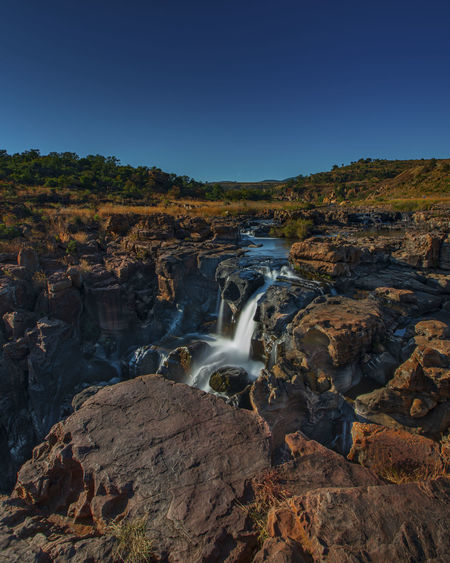 Scenic view of waterfall against clear sky