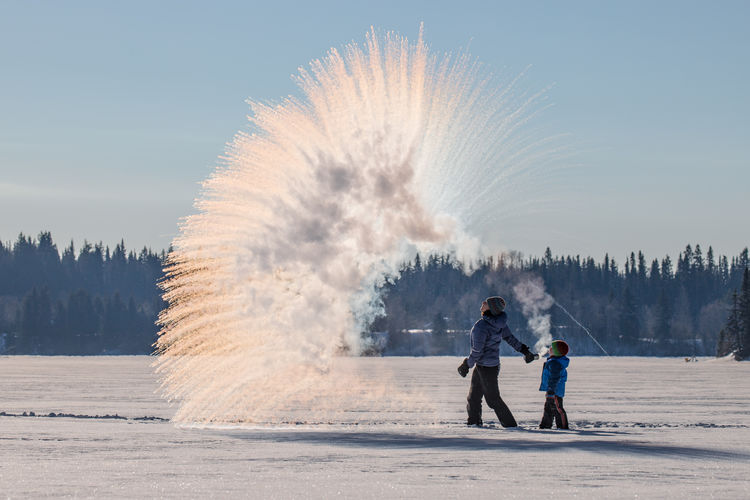 Man With Son Standing By Firework Display On Snow Covered Field