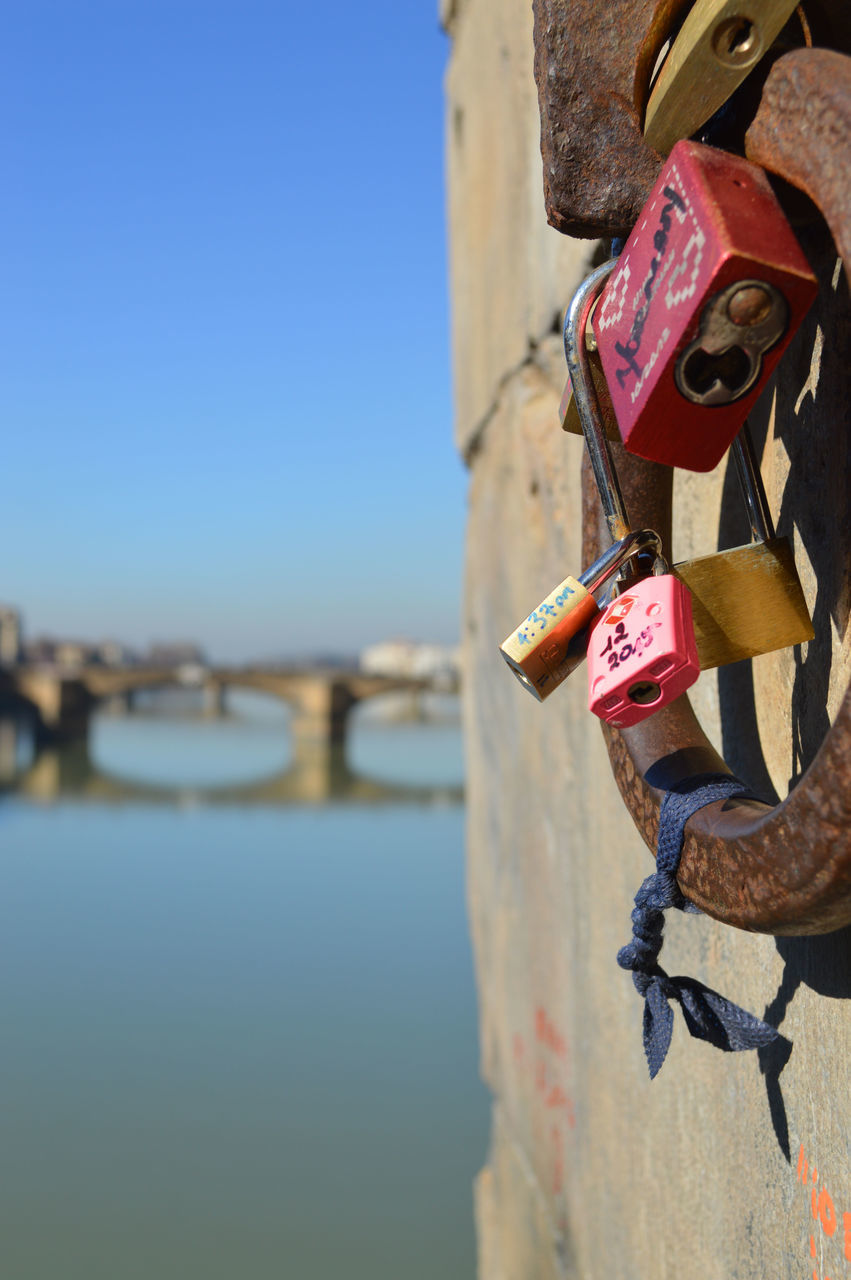 padlock, security, love lock, lock, safety, protection, hanging, outdoors, love, day, water, metal, railing, focus on foreground, hope - concept, clear sky, close-up, hope, river, sky, no people, nature