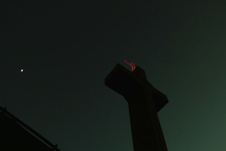 Low angle view of cross against clear sky at night