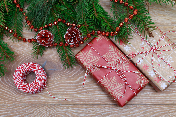 Christmas presents on a wooden floor near a Christmas tree Box Gift Box MAS New Year Ribbon Rustic Xmas Branch Celebration Christmas Christmas Decoration Christmas Is Coming Christmas Ornament Christmas Tree Decoration Flat Lay Gift No People Preparation  Present Spruse Suprise Tradition Tree Wooden Background