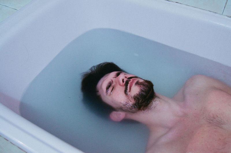 Close-Up Of Man Lying In Bathtub