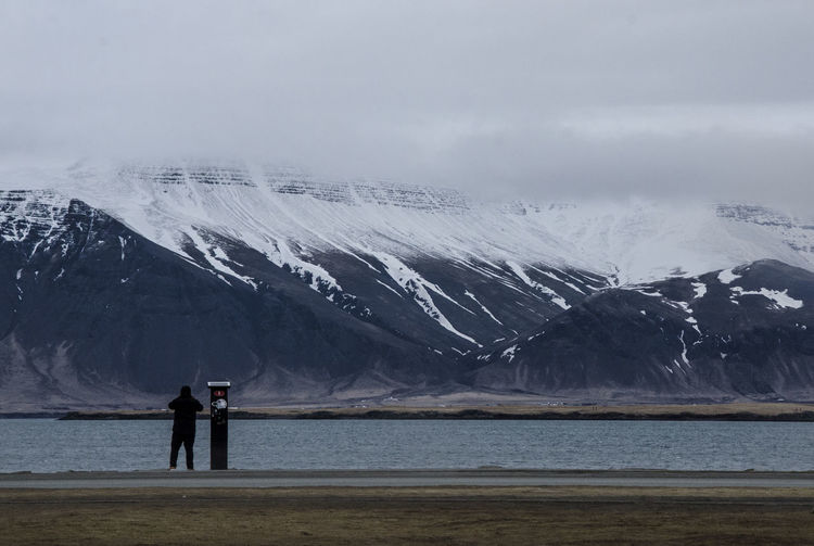 People standing on snowcapped mountain by sea against sky