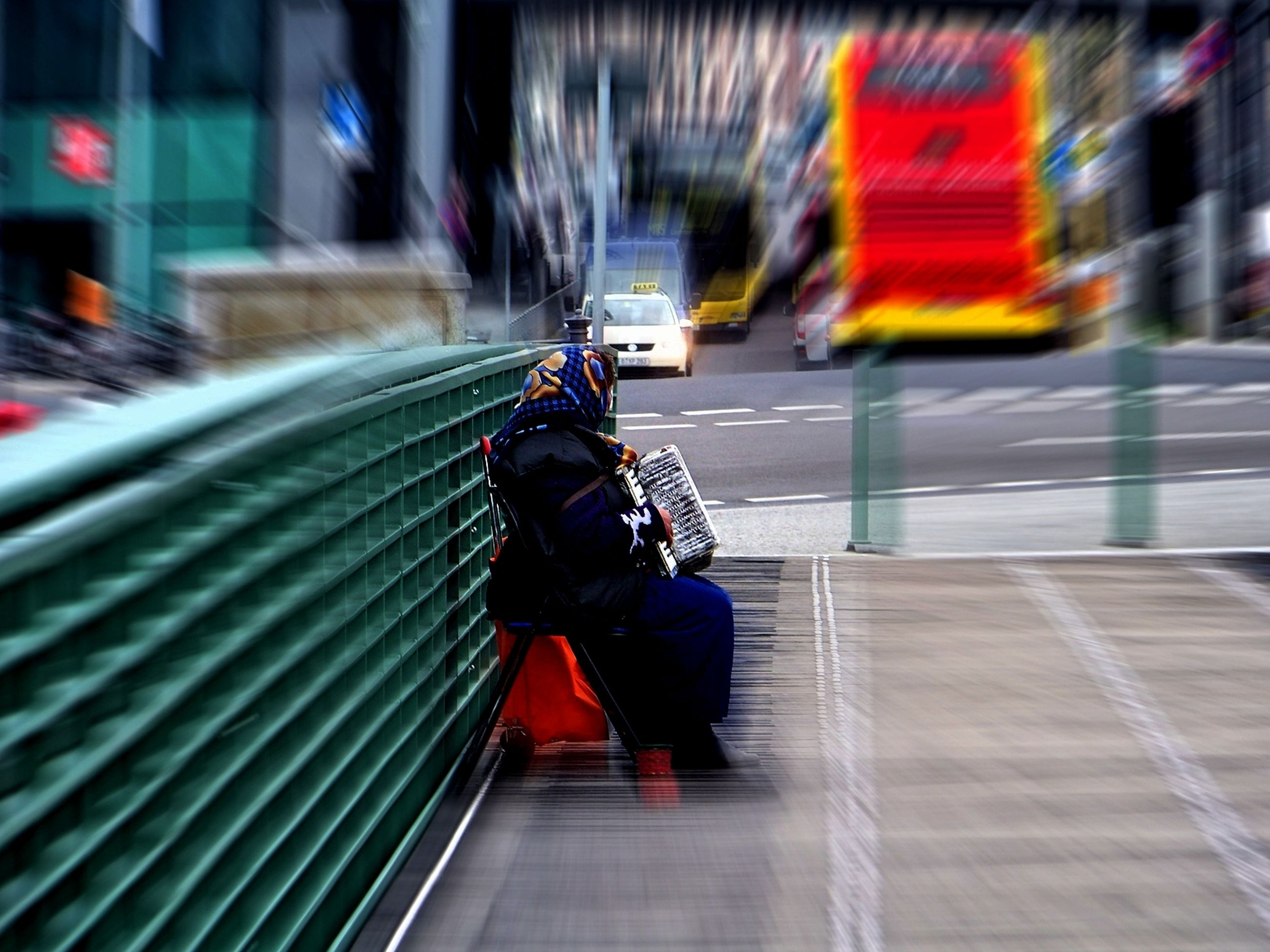 real people, lifestyles, transportation, architecture, blurred motion, motion, men, mode of transportation, leisure activity, travel, women, selective focus, rear view, city, land vehicle, railing, day, outdoors, warm clothing