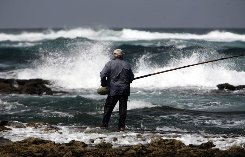 Man fishing while standing on sea shore