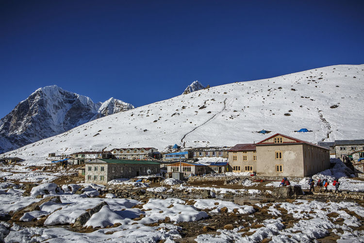 Houses against snowcapped mountains against clear blue sky