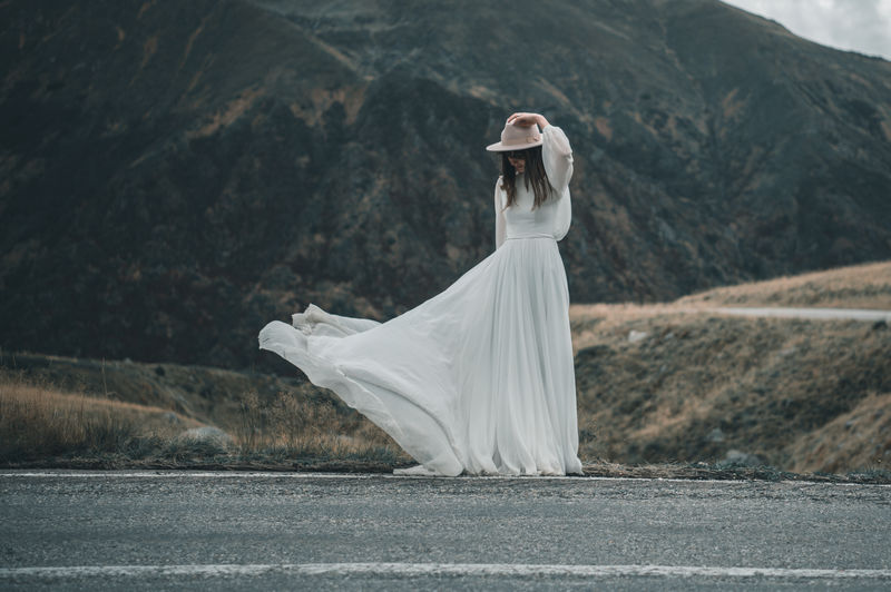 Woman standing on road by mountain