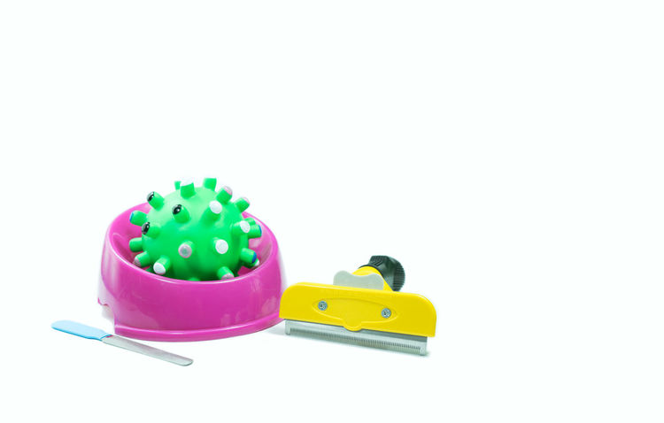 Pet accessories about rubber toys, Brush for grooming on isolated white background. Animal Representation Bowls Brush Close-up Copy Space Cut Out Design Equipment Green Color High Angle View Indoors  Multi Colored No People Pet Accessories Plastic Representation Rubber Ball Studio Shot Toy Toy Car White Background Yellow