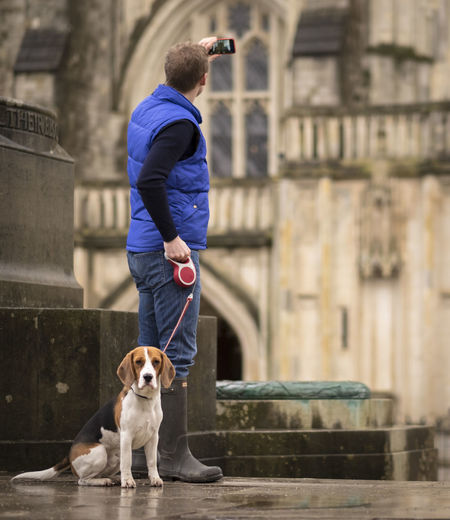 Man With Dog Photographing Building Through Mobile Phone On Footpath