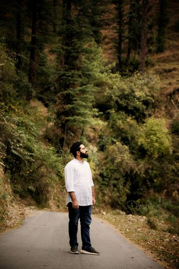 Full length of man standing on road at forest