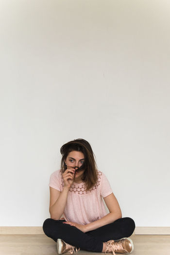 Young woman sitting against white background