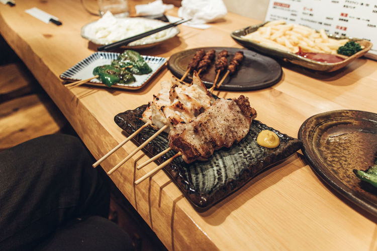 High angle view of yakitori and yakiton  served on table at izakaya restaurant in japan