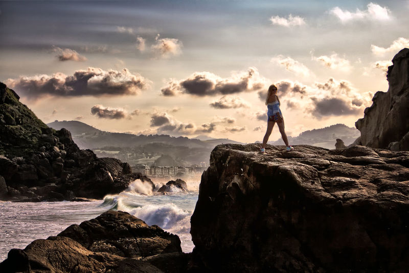 Side view of mid adult woman standing on cliff by sea against sky during sunset