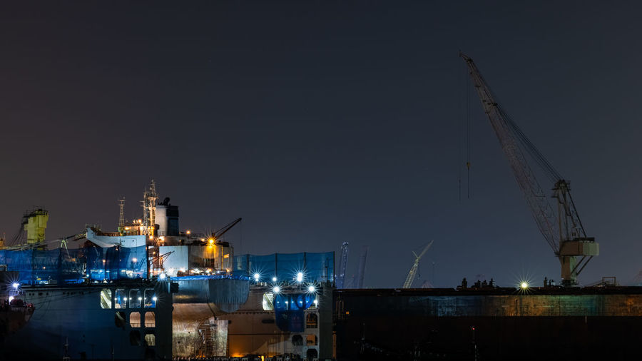 Cranes at harbor against clear sky at night