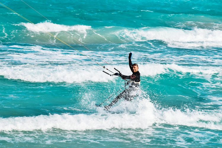 Happy man kiteboarding on sea