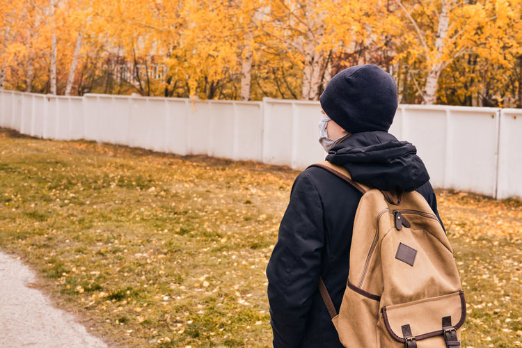 Rear view of man standing on street during autumn