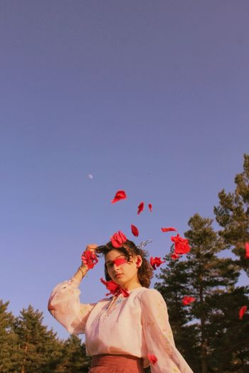 Woman standing by red tree against sky