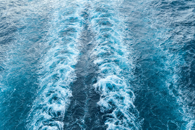 Stormy foam and a ship's track on the blue sea water.