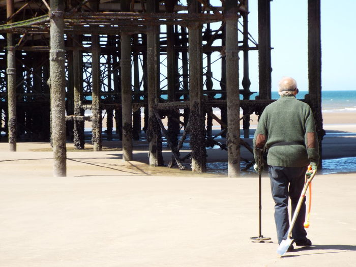 A man metal detecting under Central Pier on Blackpool Beach Man Metal Detector Metal Detecting Spade Central Pier Blackpool Central Pier Sand Summer 2016 Summertime The Essence Of Summer People People Around You People On The Beach People Walking  Beach Photography Beachphotography The Street Photographer - 2016 EyeEm Awards People Of The Oceans People And Places Finding New Frontiers