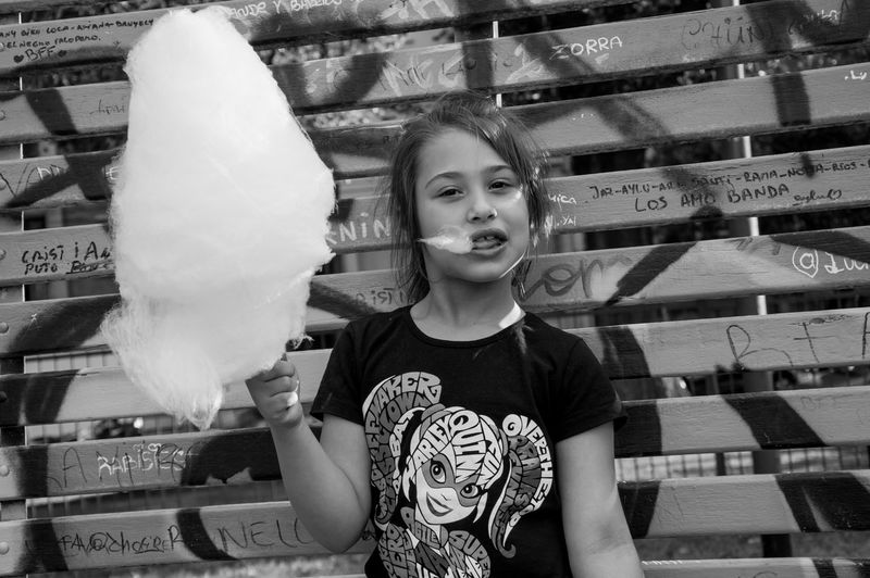 Portrait of girl with cotton candy standing against wall