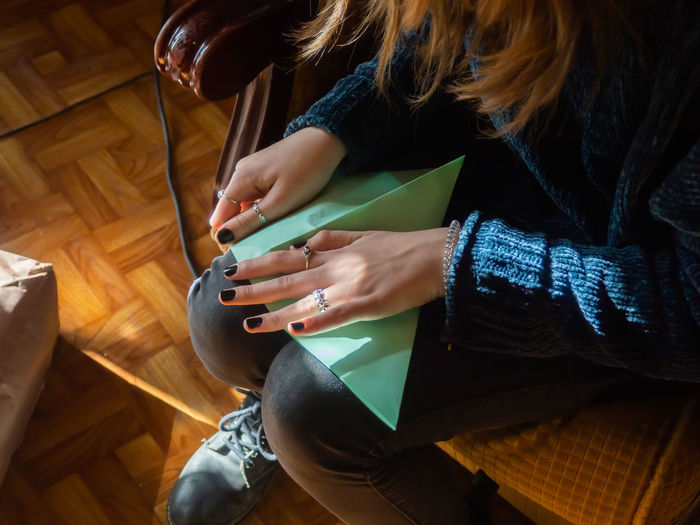 High angle view of woman holding paper while sitting at home