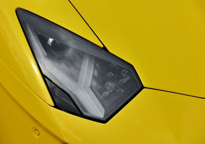 A close up detail of a Lamborghini Aventador SV headlight, with its designed style giving it an almost life like appearance to a real eye. Abstract Abstract Photography Agressive Styling Angled Lines Aventador Sv Bulls Eye Car Photography Close Up Detail Exotic Car  Eye4photography  EyeEm EyeEm Gallery Formed Glass Headlight Lamborghini Aventador Life Like Style & Design Super Car Yellow Colour