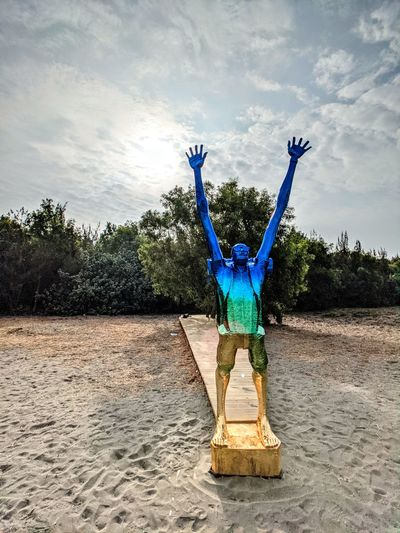 Man with arms raised in water against sky