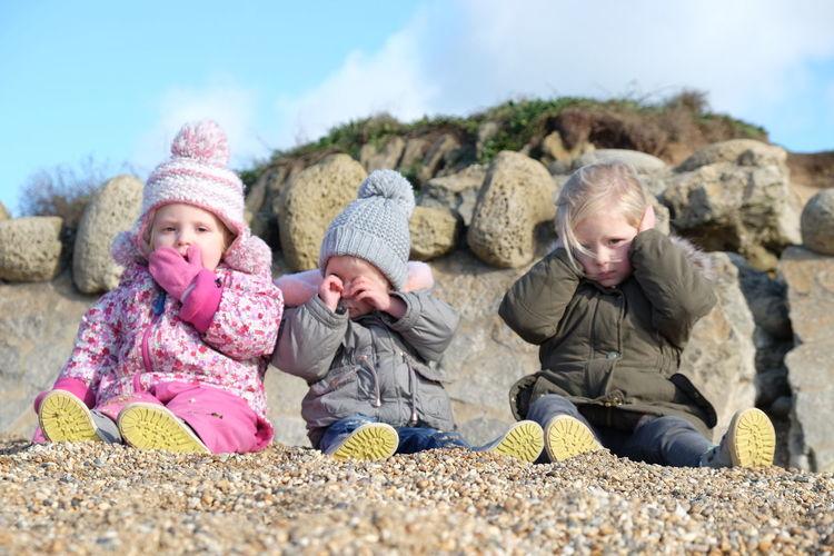Siblings Sitting At Beach Against Sky