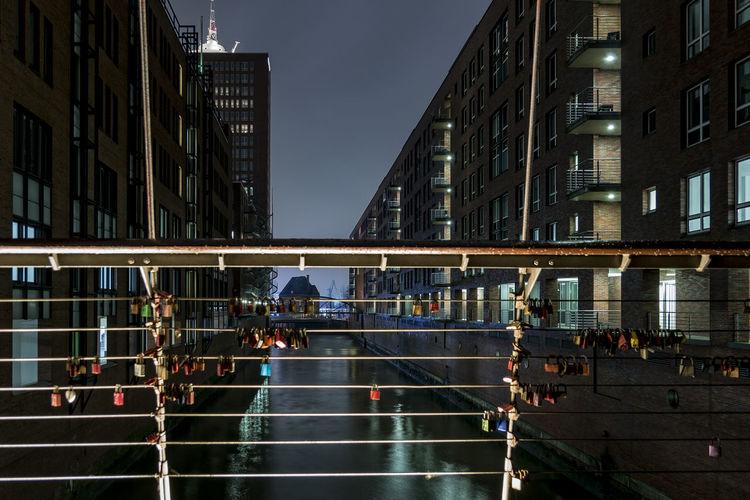 Love locks on railing of footbridge over canal amidst buildings at night in speicherstadt