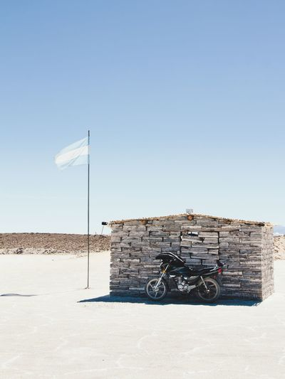 Motorcycle parked by built structure against clear sky