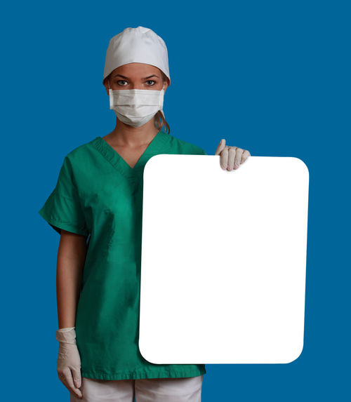 Young woman doctor keeping a white board, against a blue background. Copy Space Doctor  Healthcare Medicine Nurse White Board Adults Only Blue Blue Background Healthcare And Medicine Holding Keeping Looking At Camera Medical Cannabis Message One Person People Physician Placard Portrait Studio Shot Surgeon Surgical Mask Young Adult Young Women