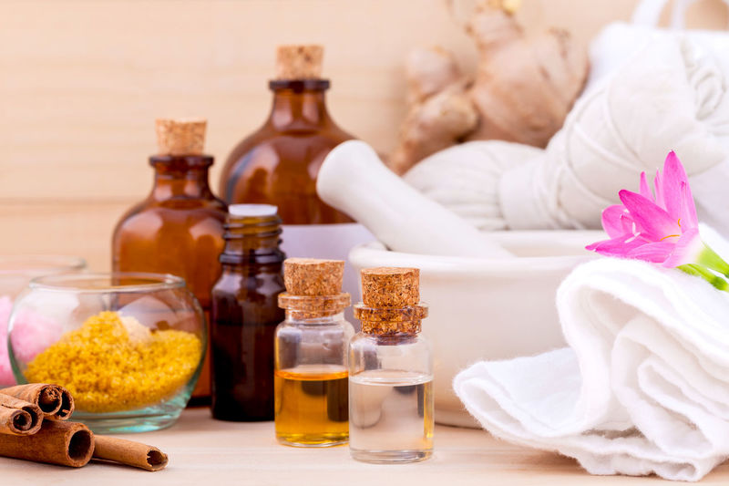 Aromatherapy products on wooden table against wall