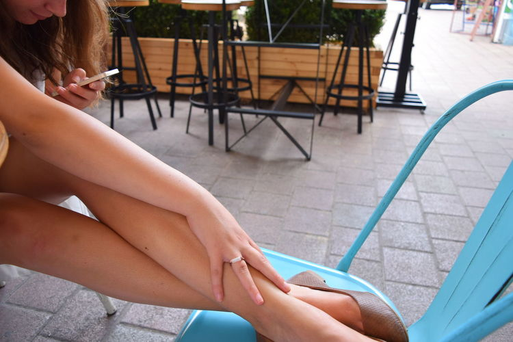High angle view of young woman using mobile phone while sitting at sidewalk cafe