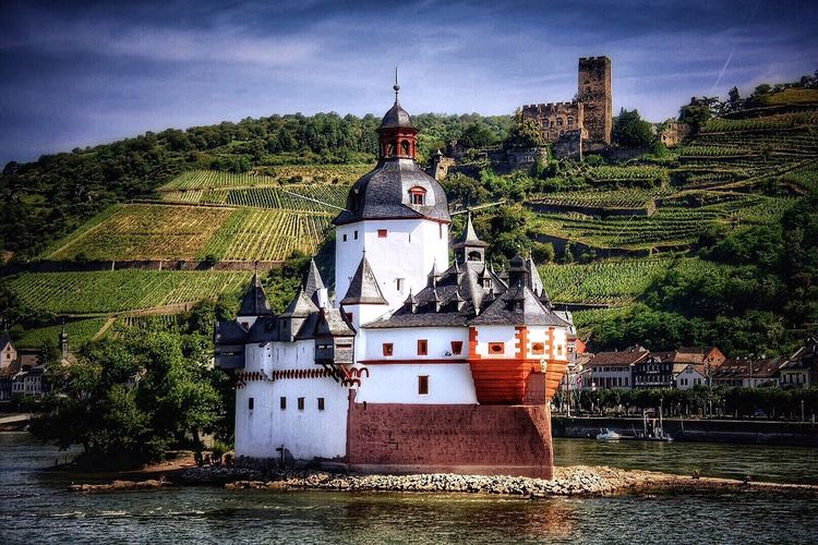 Pfalz castle by river rhine against agricultural field