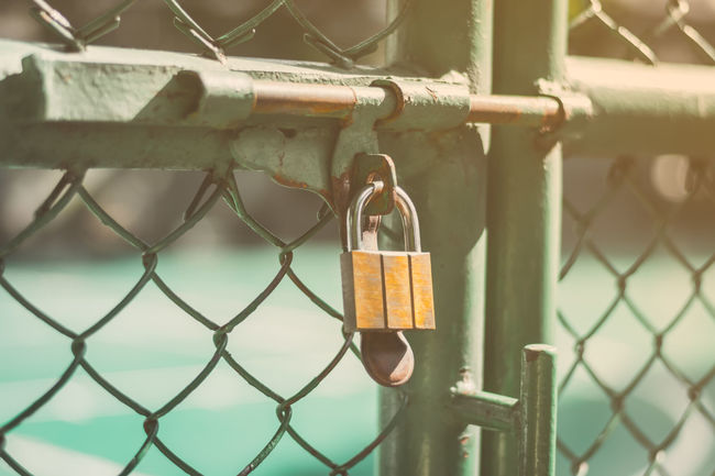 Close up of old rusty lock on green fence with sunlight.Locks on the net.Blurred background. Gate Locks Wall Backgrounds Border Chain Chainlink Fence Close-up Day Fence Hanging Hope Lock Love Love Lock Luck Metal No People Outdoors Padlock Protection Railing Safe Safety Security