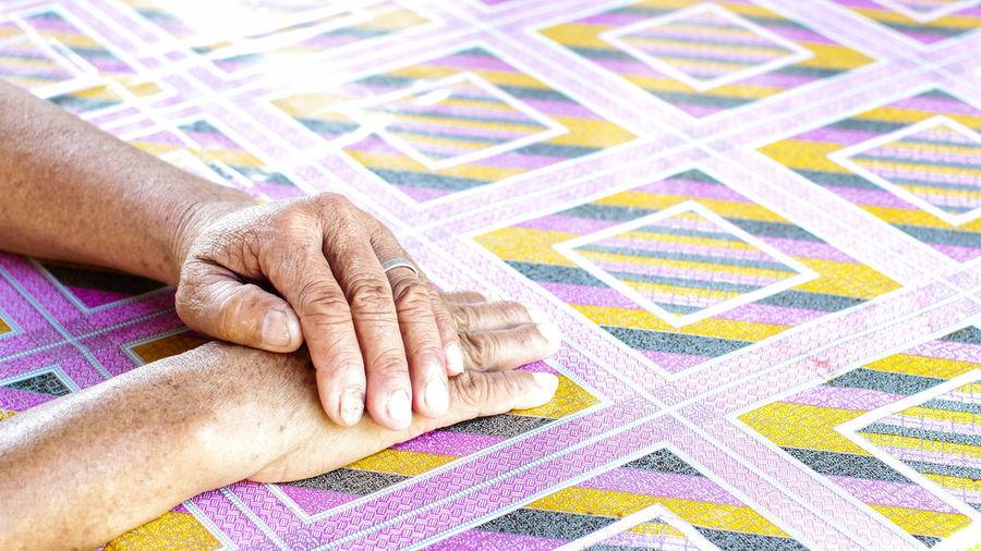 Cropped hands on patterned tiled floor
