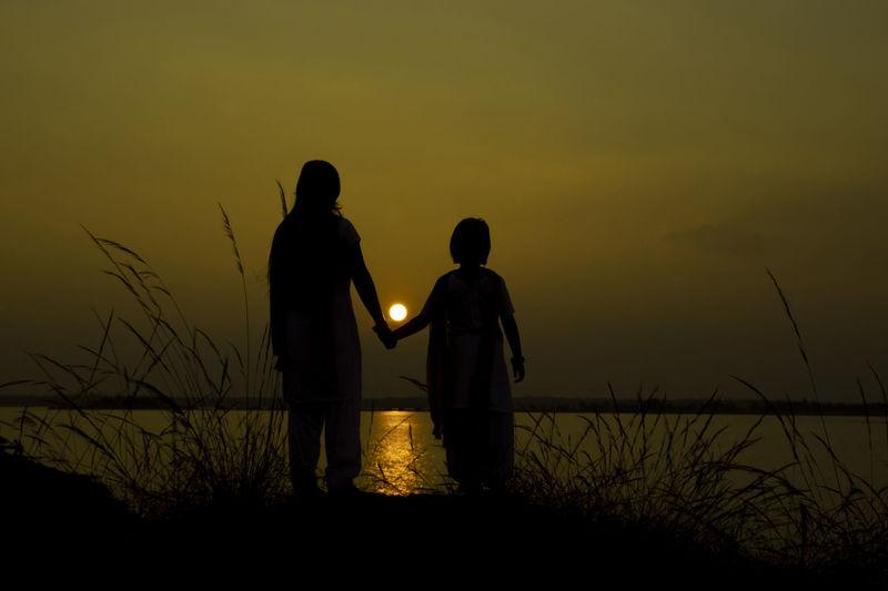 Silhouette men standing on shore against sky during sunset