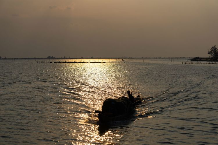 Silhouette fishing boat with beautiful nature. Rural Silhouette Sunlight Transport Transportation Bay Beauty In Nature Boat Countryside Estuary Fisherman Fishing Fishing Boat Fishing Industry Lifestyles Nature Outdoors Rural Scene Scenics - Nature Sky Sunset Tranquil Scene Tranquility Water Waterfront