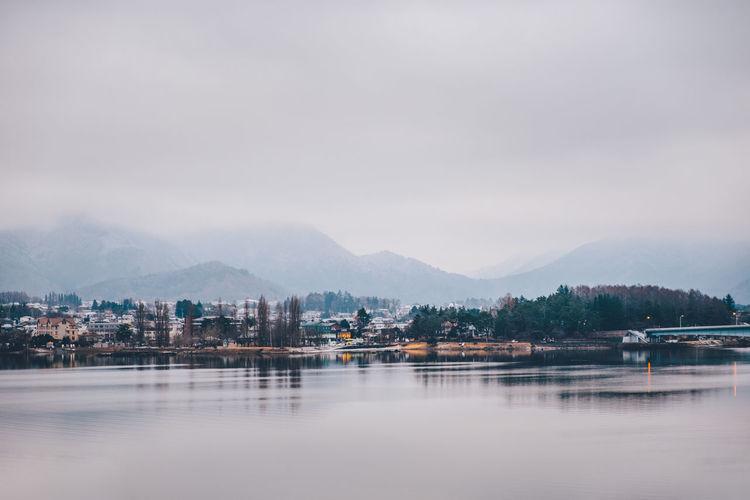 Lake by buildings in city against sky