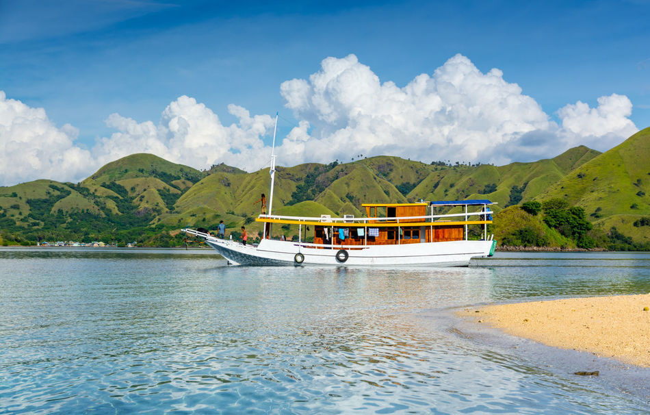 Tourist Boats At The Coast of Kelor Island, in Komodo National Park, Labuan Bajo, Flores, Indonesia Clear Sky Wave Beach Beauty In Nature Cloud - Sky Day Island Kelor Island Komodo Mountain Nature Pinnacle Pulau Scenics - Nature Sea Shadow Sky Tranquil Scene Tranquility Transparent Water