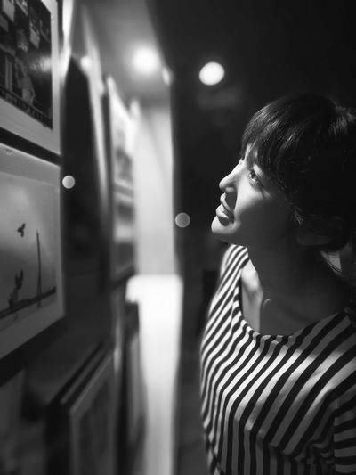 Smiling young woman looking at picture frames