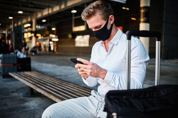 Man using mobile phone while sitting on seat